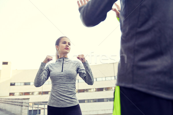 woman with trainer working out self defense strike Stock photo © dolgachov