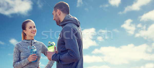 smiling couple with bottles of water over blue sky Stock photo © dolgachov