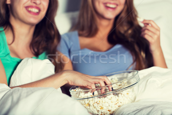 happy women eating popcorn and watching tv at home Stock photo © dolgachov
