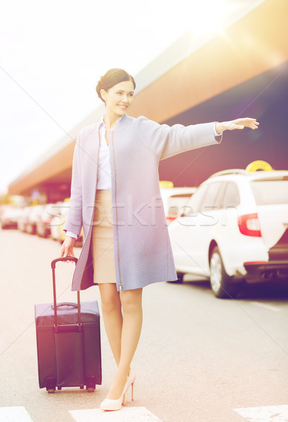 smiling young woman with travel bag catching taxi Stock photo © dolgachov