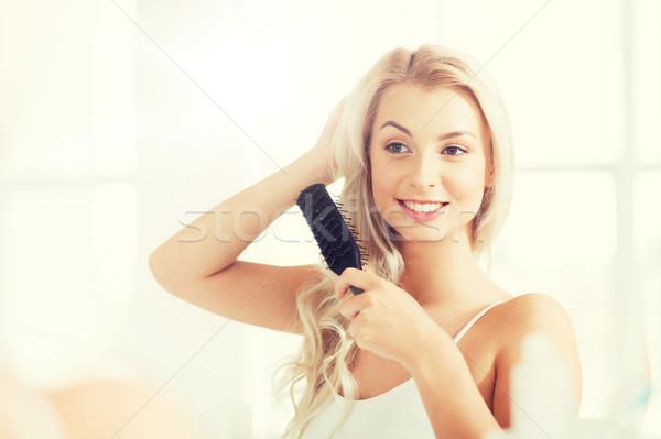 happy woman brushing hair with comb at bathroom Stock photo © dolgachov