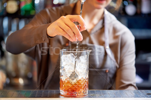 bartender with cocktail stirrer and glass at bar Stock photo © dolgachov