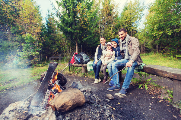 Familia feliz sesión banco campamento fuego camping Foto stock © dolgachov