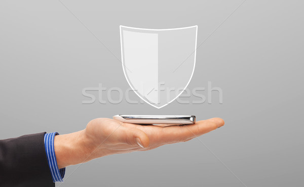hand with smartphone and antivirus program icon Stock photo © dolgachov