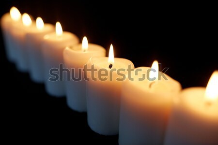 candles burning in darkness over black background Stock photo © dolgachov
