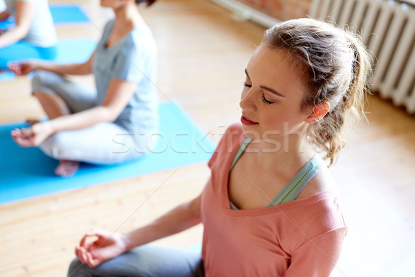 woman meditating at yoga studio Stock photo © dolgachov