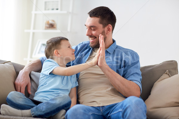father and son doing high five at home Stock photo © dolgachov