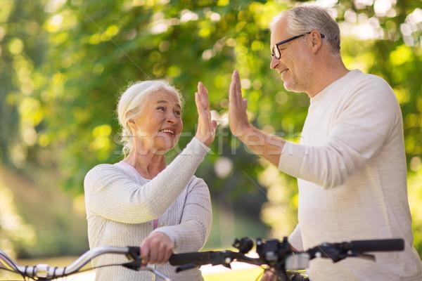 senior couple with bikes making high five at park Stock photo © dolgachov