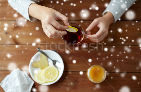 close up of ill woman adding lemon to tea cup Stock photo © dolgachov