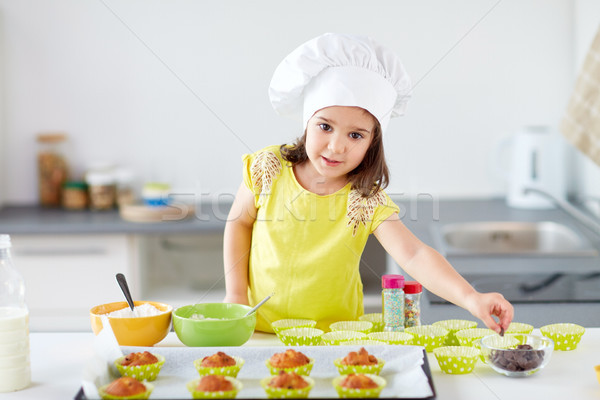 little girl in chefs toque baking muffins at home Stock photo © dolgachov