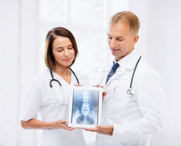 two doctors showing x-ray on tablet pc Stock photo © dolgachov