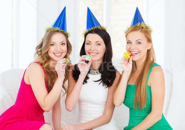 three smiling women in hats blowing favor horns Stock photo © dolgachov