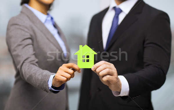 businessman and businesswoman holding green house Stock photo © dolgachov
