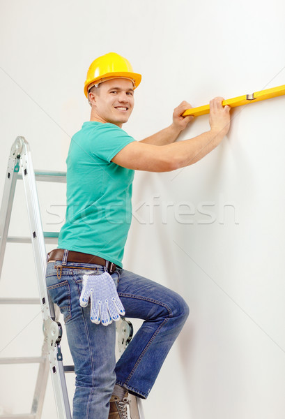 smiling man building using spirit level to measure Stock photo © dolgachov