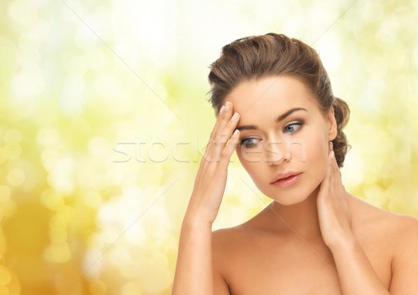 Femme mains tenant cou front santé beauté Photo stock © dolgachov