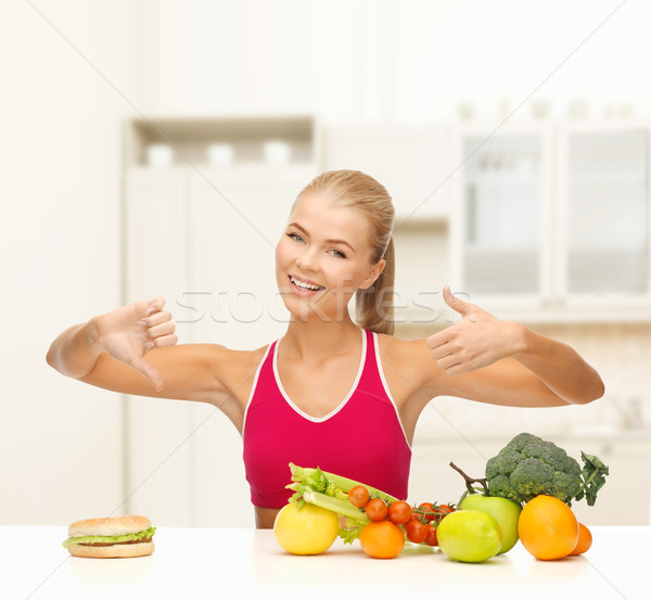 woman with fruits and hamburger comparing food Stock photo © dolgachov