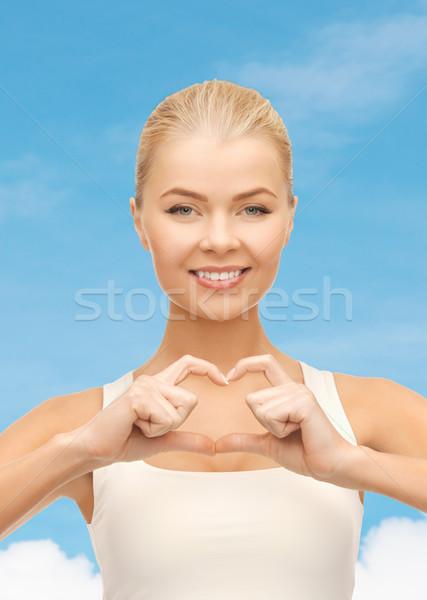Foto d'archivio: Donna · sorridente · a · forma · di · cuore · gesto · amore · felicità