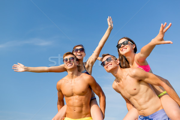 Stock photo: smiling friends having fun on summer beach