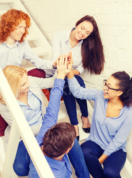 team doing high five gesture sitting on staircase Stock photo © dolgachov