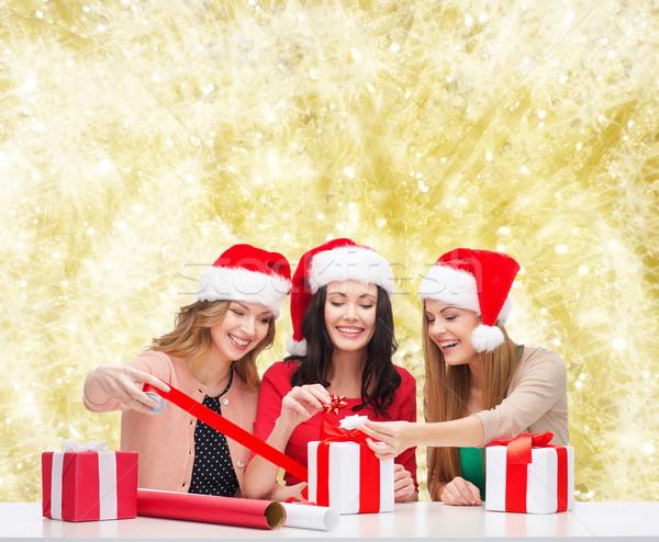 smiling women in santa helper hats packing gifts Stock photo © dolgachov