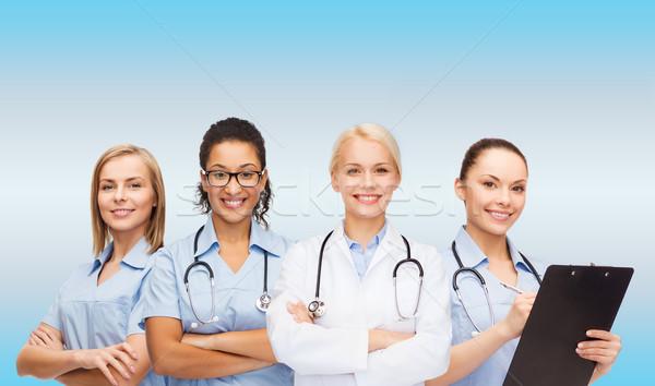 smiling female doctor and nurses with stethoscope Stock photo © dolgachov