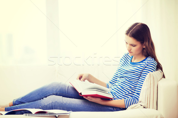 calm teenage girl reading book on couch Stock photo © dolgachov