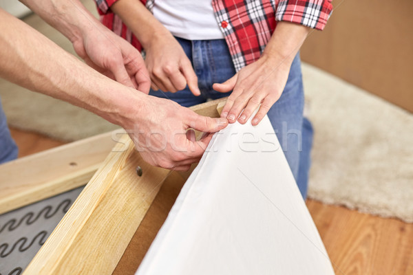 close up of couple assembling furniture at home Stock photo © dolgachov