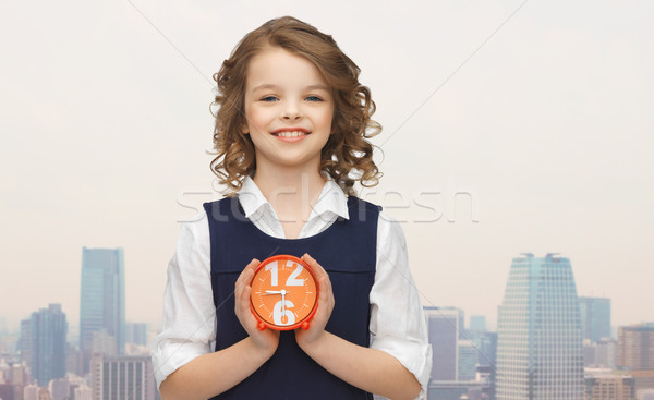 happy girl with alarm clock over city background Stock photo © dolgachov