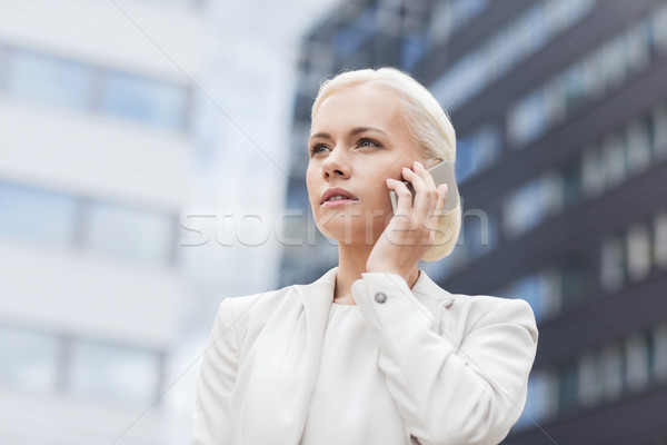 Stock photo: serious businesswoman with smartphone outdoors