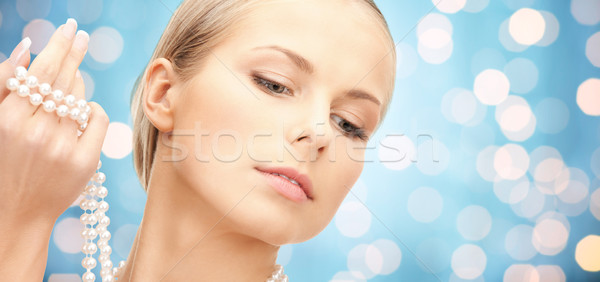 beautiful woman with pearl beads in hand Stock photo © dolgachov