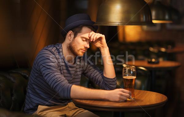 unhappy lonely man drinking beer at bar or pub Stock photo © dolgachov