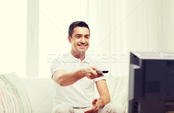 Souriant homme télécommande regarder tv maison Photo stock © dolgachov