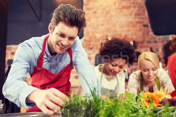 happy friends cooking and decorating dishes Stock photo © dolgachov