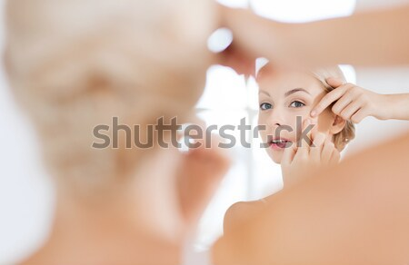 woman squeezing pimple at bathroom mirror Stock photo © dolgachov