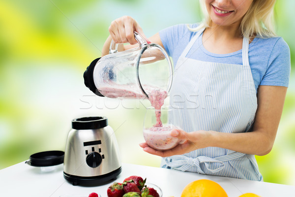 Stock photo: close up of woman with blender and shake at home