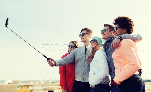 friends taking selfie with smartphone on stick Stock photo © dolgachov