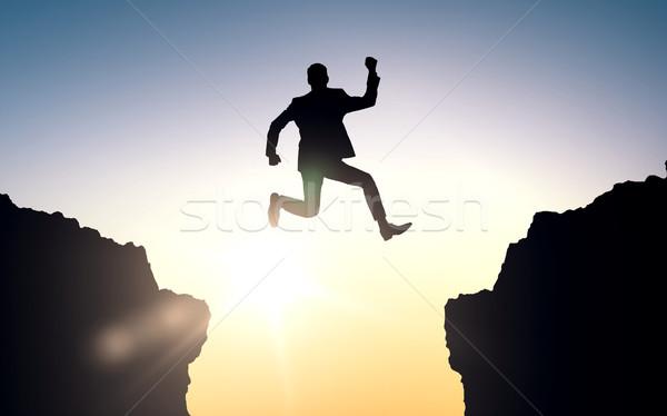Feliz empresario saltar rocas gente de negocios éxito Foto stock © dolgachov