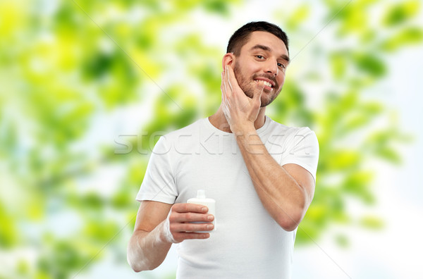счастливым молодым человеком кремом лосьон лице Сток-фото © dolgachov