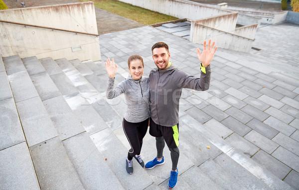 happy couple waving hands outdoors on city street Stock photo © dolgachov