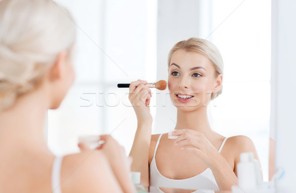 woman with makeup brush and powder at bathroom Stock photo © dolgachov