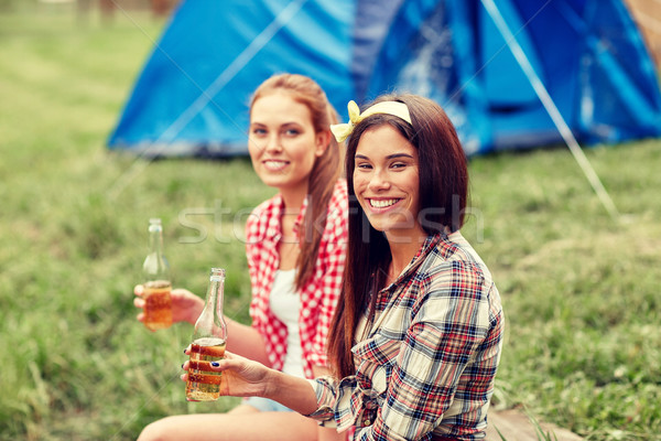 happy young women with tent and drinks at campsite Stock photo © dolgachov