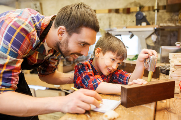 dad and son with ruler measuring plank at workshop Stock photo © dolgachov