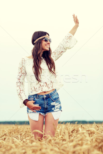 smiling hippie woman on cereal field waving hand Stock photo © dolgachov