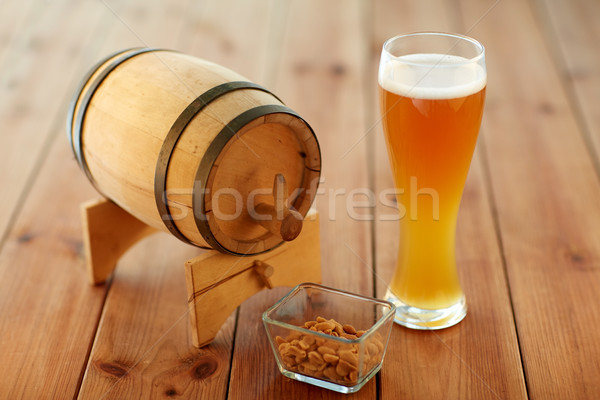 close up of beer glass, peanuts and wooden barrel Stock photo © dolgachov