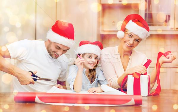 smiling family in santa helper hats with gift box Stock photo © dolgachov