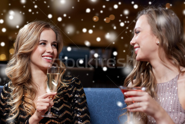 happy women with drinks at night club over snow Stock photo © dolgachov