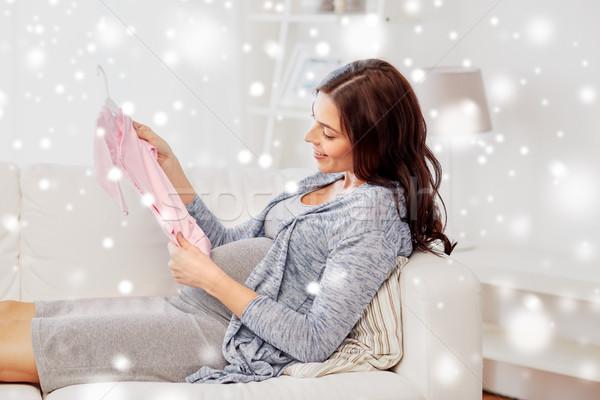 happy woman holding baby girls bodysuit at home Stock photo © dolgachov