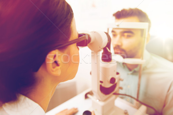 optician with slit lamp and patient at eye clinic Stock photo © dolgachov