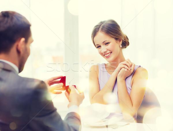 Animado mulher jovem olhando namorado anel restaurante Foto stock © dolgachov