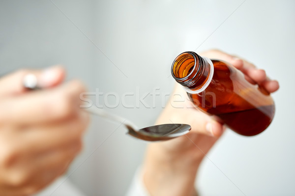 woman pouring medication from bottle to spoon Stock photo © dolgachov